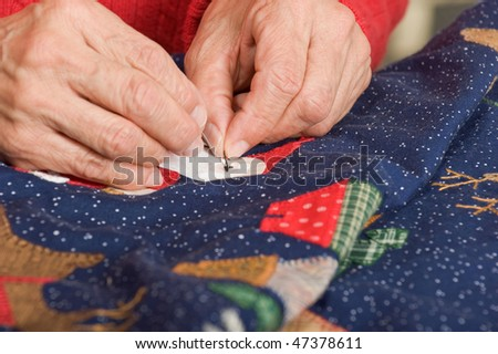 A quilter sewing a french knot for santa's eyes - stock photo