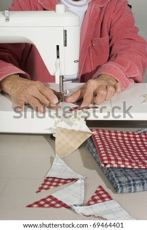 A quilter stitches cut pieces of colorful fabric for a quilt top. - stock photo