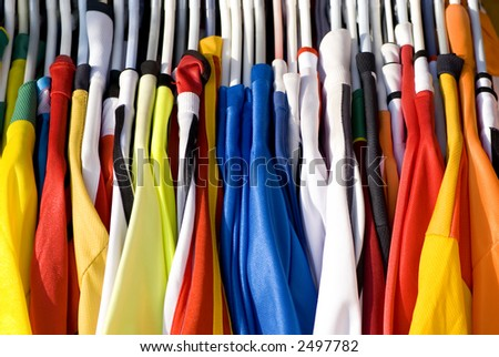 A rack of colorful shirts (Jerseys) for sale at an open market - stock photo