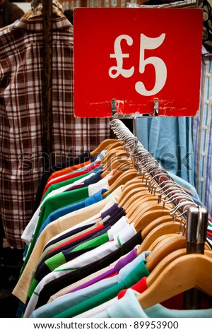A rack of second-hand shirts and t-shirts at a market in London, all for a fiver: recession bargains. - stock photo
