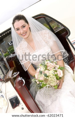 A radiant looking bride getting out of wedding car - stock photo