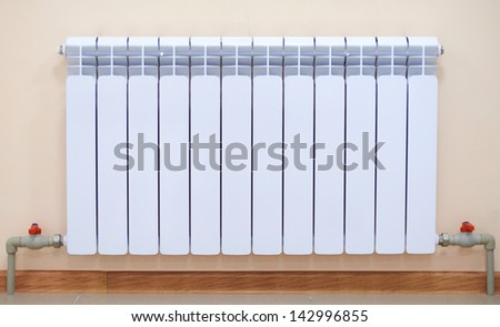A radiator, pipes and taps. - stock photo