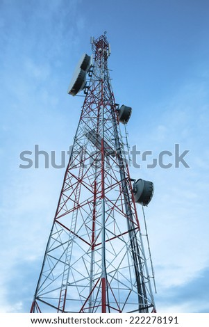 A radio communications tower under blue sky before sunset