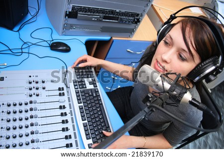 A radio DJ announces news in a studio - stock photo