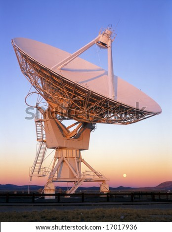 A Radio Telescope, part of the Very Large Array (VLA), in New Mexico with the full moon. - stock photo