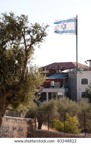 A ragged Israeli flag flies over the Jewish settlement of Beit Hoshen on the Mount of Olives in East Jerusalem. - stock photo