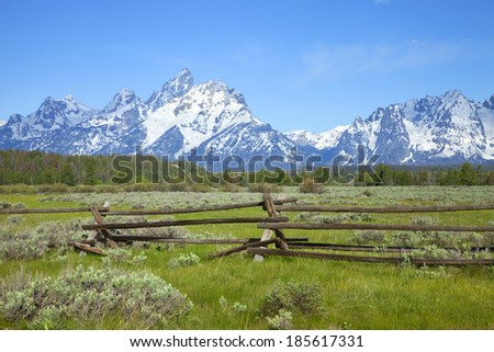 A rail ranch fence crosses a field below the Grand Teton mountains in Wyoming - stock photo