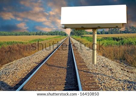 A railroad going thru a farm with a roadside billboard - stock photo
