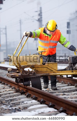 a railroad worker repairs rails with his machine - stock photo