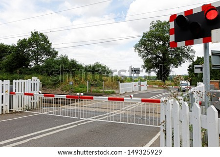 A railway level crossing in the UK countryside, with barriers closed and lights flashing - stock photo
