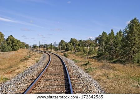 a railway track curves through a rural countryside - stock photo