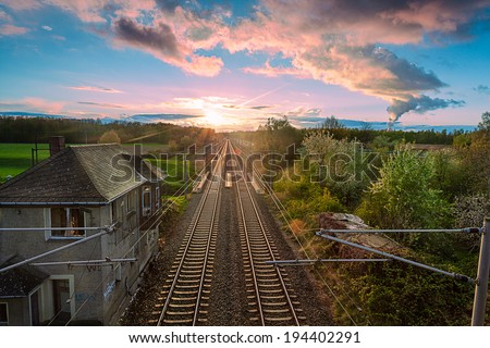 a railway whit an Vanishing point in the distance and sunrise - stock photo