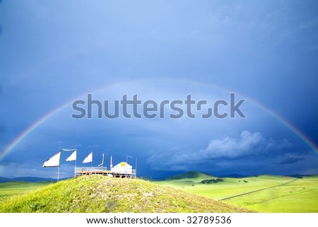 A rainbow arched across the sky and grassland - stock photo