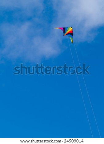 A rainbow colored stunt kite against a blue sky with wispy clouds. - stock photo