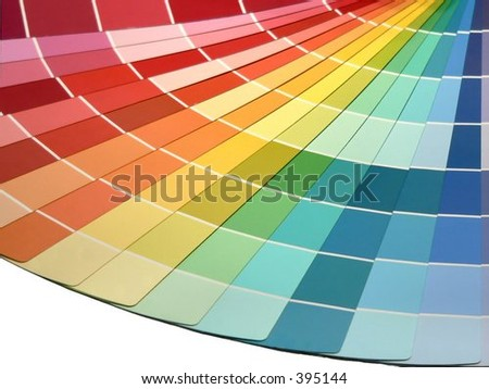 A rainbow is created from selection samples of vivid toned paint colors fanned out. Isolation on white across the bottom gives room to create copy space. Red to orange to yellow to green to blue.