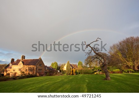 A rainbow over a traditional manor house and garden in England in winter. Cloudy sky overhead with copyspace for your text/design. - stock photo