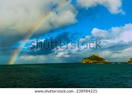 A rainbow over deep harbor in Antigua - stock photo