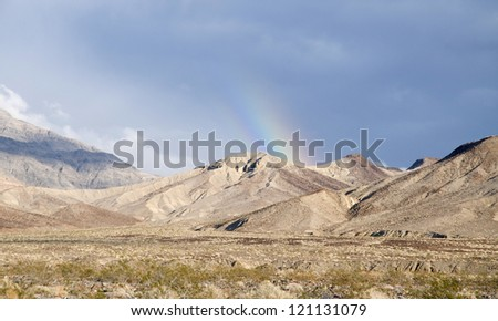 A rainbow over the mountains in Death Valley National Park. - stock photo
