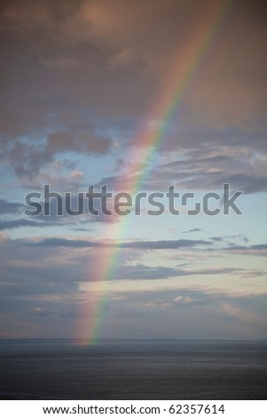 A rainbow over the sea in the sunset - stock photo