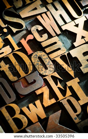 A random selection of wooden letterpress characters as a background, narrow focus. - stock photo