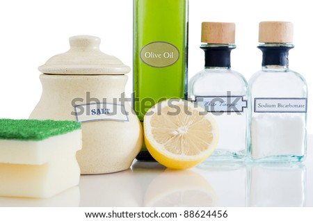 A range of natural, non-toxic cleaning products in containers on a shiny reflective surface with a white background. - stock photo