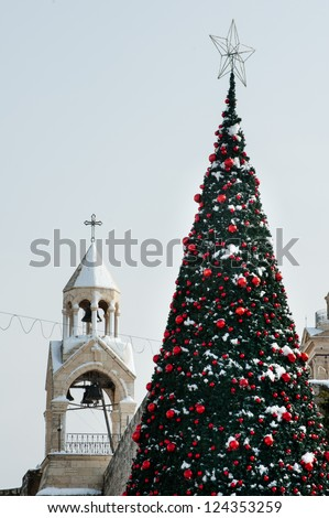 A rare snowfall lies on a Christmas tree standing near the Church of the Nativity, traditional site of the birthplace of Jesus Christ in the West Bank town of Bethlehem. - stock photo