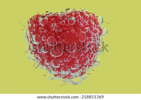 A Raspberry in Clear Fizzy Water Against a Yellow Background. - stock photo