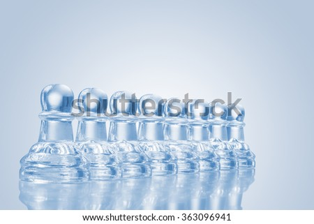 A raw of transparent glass pawns on reflective surface. - stock photo