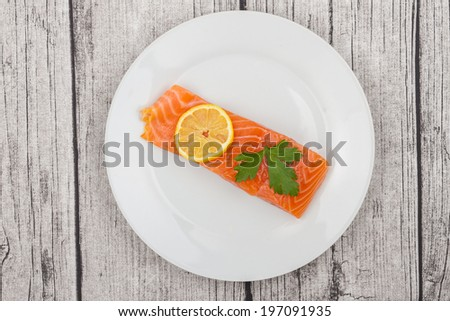 A Raw Salmon Fillet on a Rustic Table - stock photo