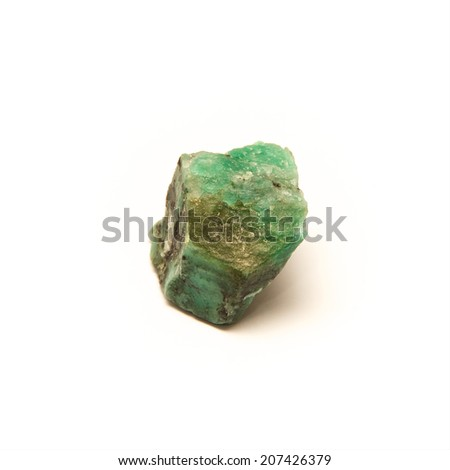 A raw uncut piece of emerald shot over white. - stock photo
