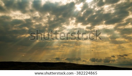 a ray of light in the gloomy sky - stock photo