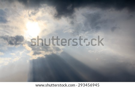 A ray of sunlight breaking through dark clouds. - stock photo