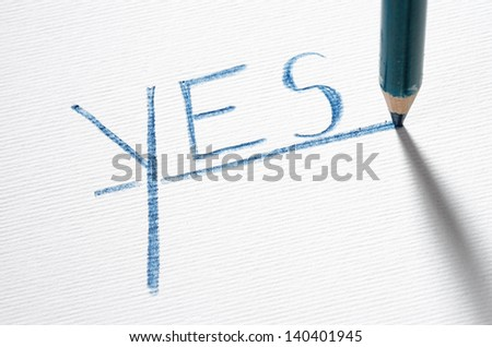 A rblue pastel pencil writing the word YES - stock photo
