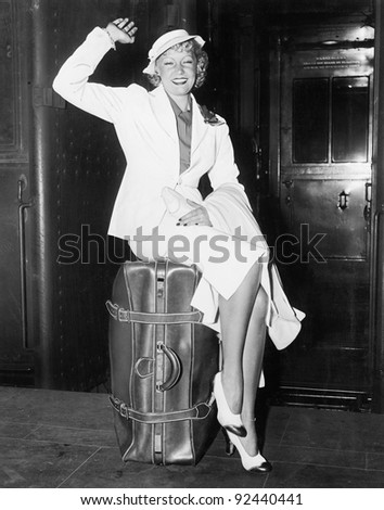 A ready to go young woman sitting on her suitcase and waving - stock photo