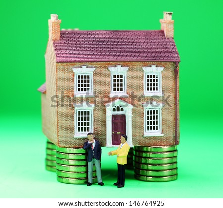 A real estate agent and a prospective buyer in front of a house on gold coin stilts, with the prospective buyer baulking with a real thinkers pose, suggesting you have to find the buyers green button! - stock photo