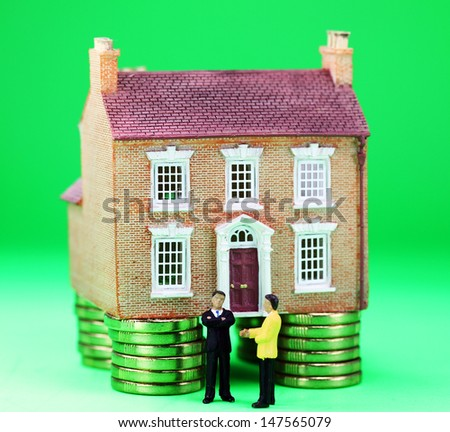 A real estate agent and a prospective buyer in front of a house on gold coin stilts, with the prospective buyer not impressed with very negative body language, suggesting you can't win them all! - stock photo