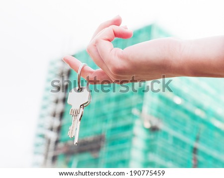 A real estate agent holding keys to a new apartment in her hands. Real estate industry - stock photo