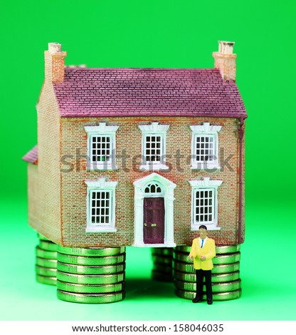 A real estate agent in front of a house on gold coin stilts, asking the question how much money will you have to invest to purchase this property?  - stock photo