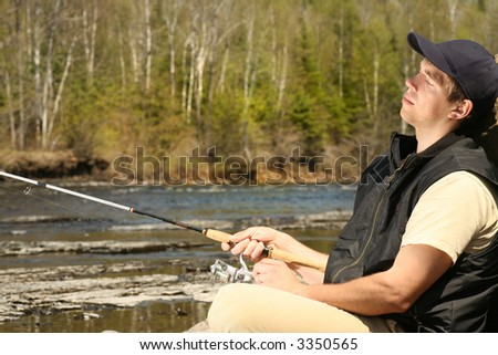 a really relaxed looking fisherman sitting on the rocks by the river