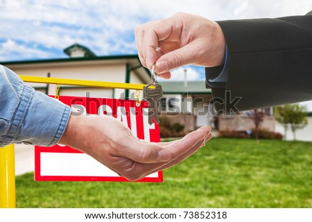 A  realtor handing over keys to a buyer in-front of a house
