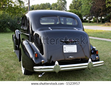 A rear side view of a black vintage Buick - Emblems removed - 1930's? - stock photo