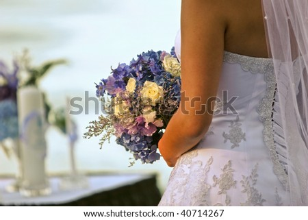 A rear view of a bride holding a bouquet - stock photo