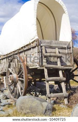 A rear view of a covered wagon used on the Old Oregon Trail. It has  a weathered wooden ladder leaning on it. - stock photo