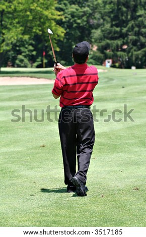 A rear view of a male golfer completing golf drive from fairway. - stock photo