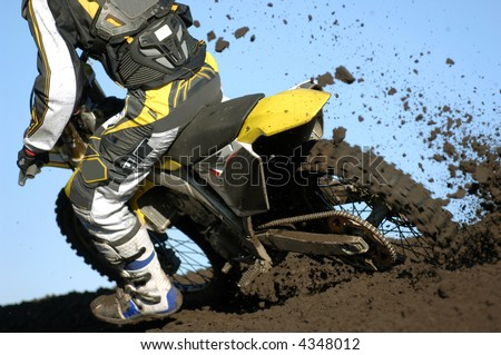 A rear view of a motocross rider races through the dirt and mud during a race. - stock photo