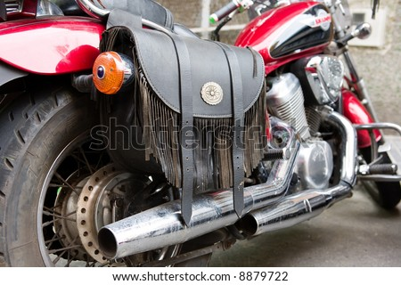 A rear view of a motorcycle with chromed exhaust pipes