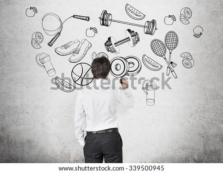 A rear view of a person in formal clothes who is drawing a range of sport activities and sport equipment on the concrete wall. A concept of gym culture among office clerks. - stock photo