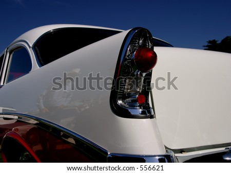 A rear view of a retro classic car with a reflection of a cowboy on the side of the car.