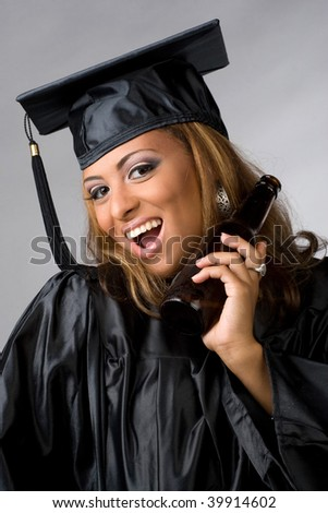 A recent graduate posing in her cap and gown holding beer bottle isolated over a silver background. - stock photo