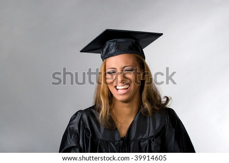 A recent graduate posing in her cap and gown isolated over a silver background. - stock photo
